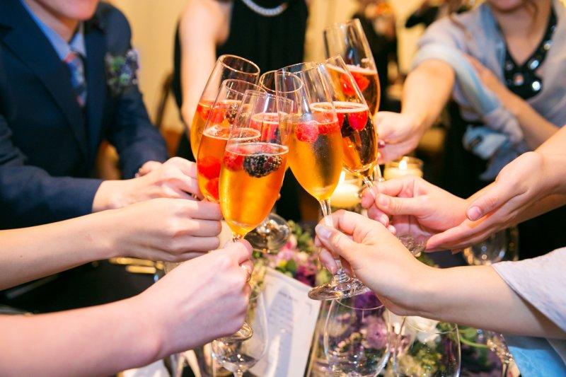 パーティーで男女複数人が乾杯している