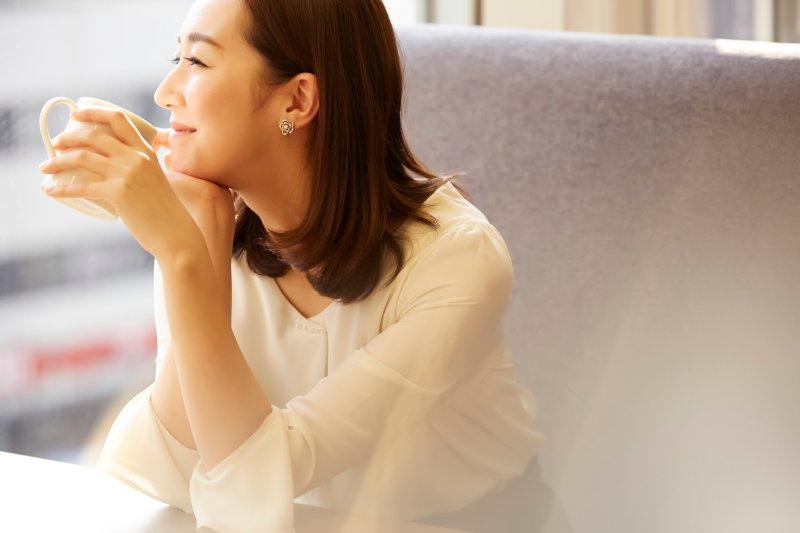 肘をテーブルについて右手を顎につけて笑顔で外を眺める女性