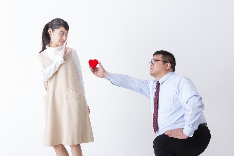 跪いて右手のハートを女性に渡そうとしている男性とそれを断っている女性