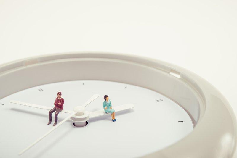 時計の針に座る男性と女性