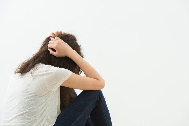 頭を抱えて座り込む女性