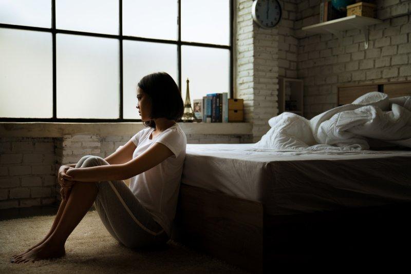 足を抱えて床に座る女性