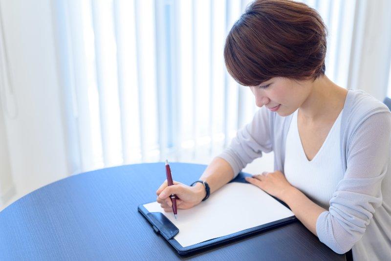 テーブルに座った女性がバインダーでとめている紙に何かを記入している