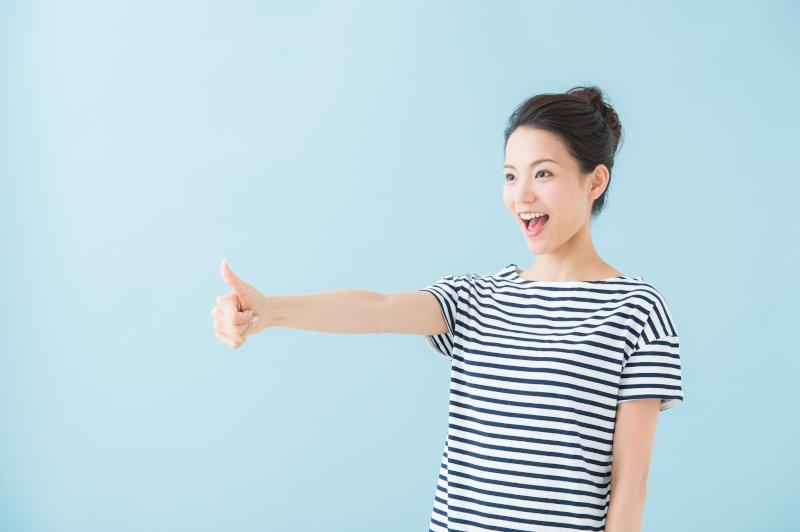 右手親指を立てて前に掲げている女性