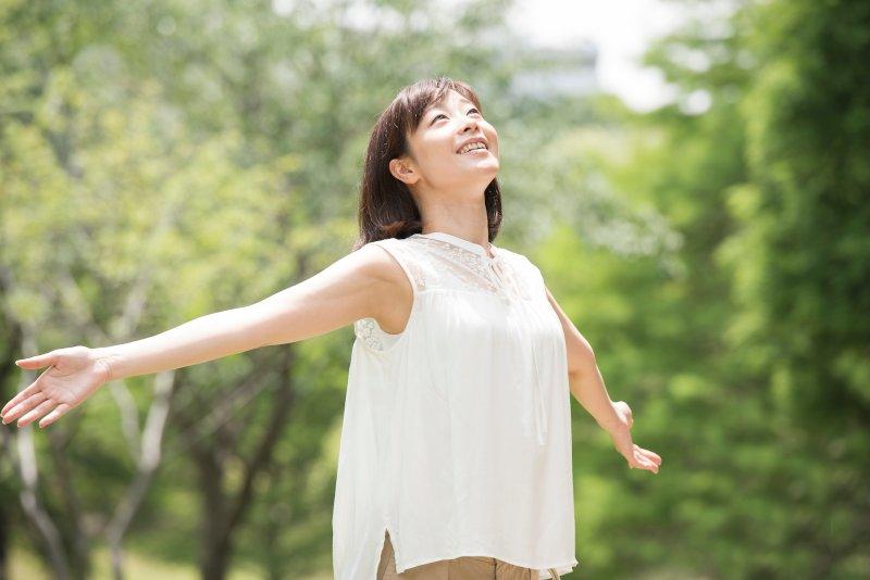 自然の中で両手を広げて深呼吸している女性