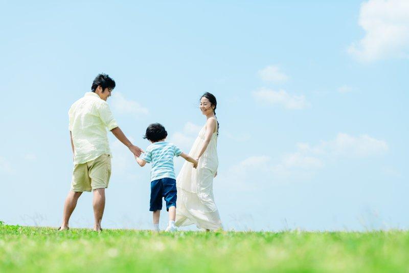 野原を歩く3人家族