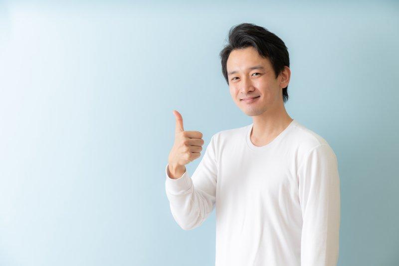 右手親指を立てている笑顔の男性