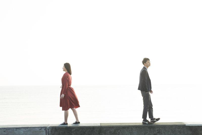 堤防の上で左右に分かれて歩いていく男女