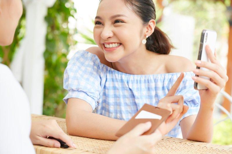 スマホを見せる笑顔の女性