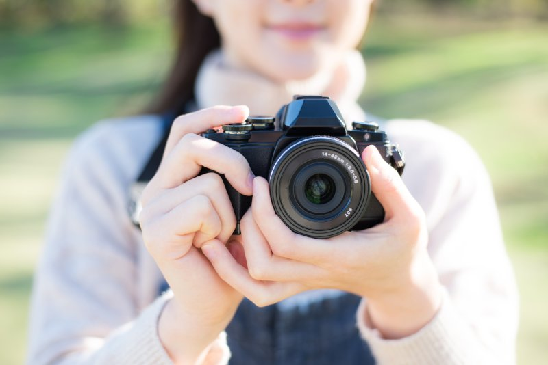 一眼レフカメラを持つ女性
