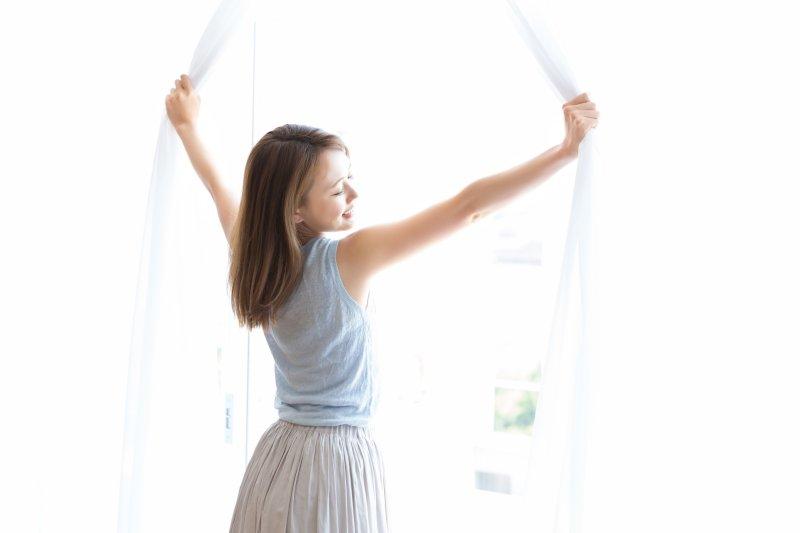 カーテンを開け気持ちと空気を入れ替える女性