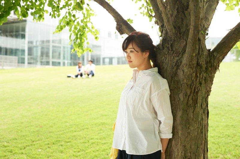 木の下でぼーっとする女性