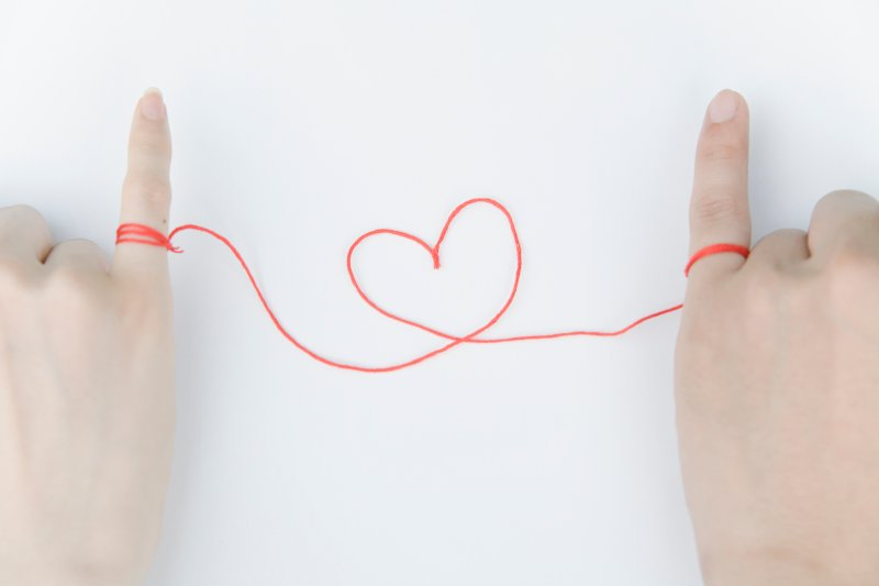 カップルの小指が赤い糸で結ばれている