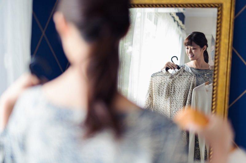 女性が鏡の前で洋服を合わせている
