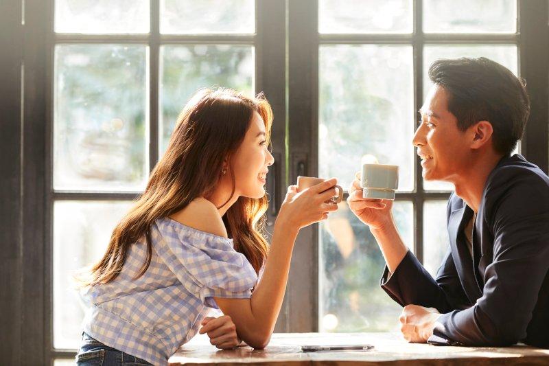 テーブル越しに会話するカップル