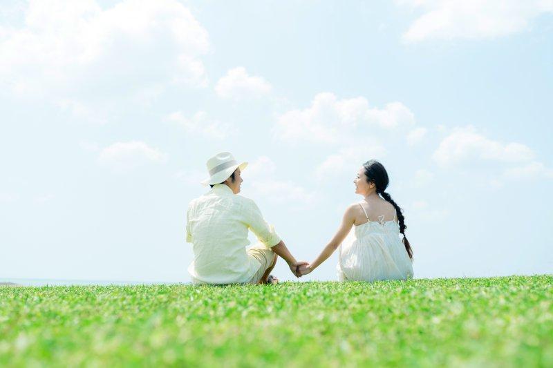 芝生の上でカップルが手をつないで座っている