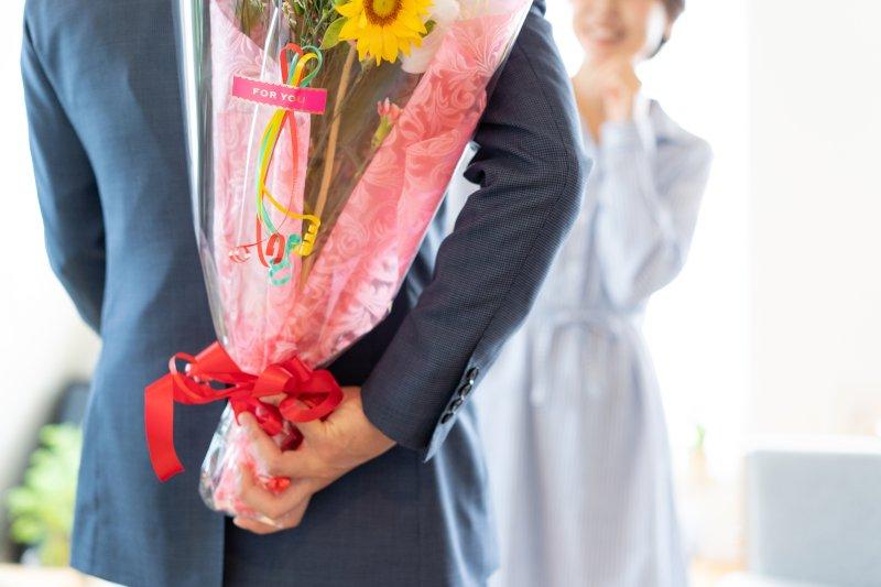 女性を前にして花束を背後に持つ男性