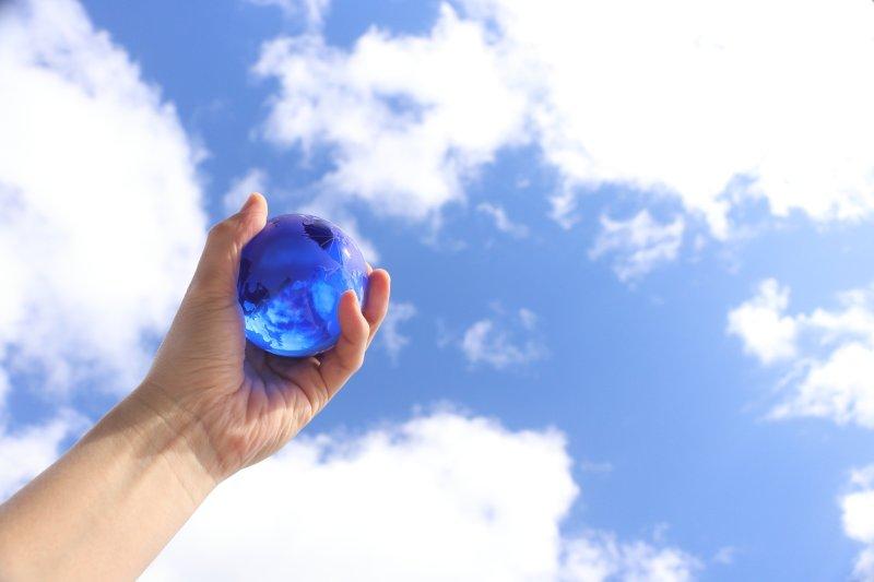 クリスタルの地球を空に掲げている手