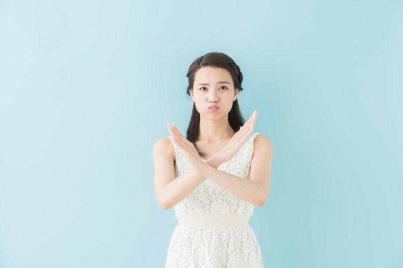 胸の前で両腕バツ印を作る女性