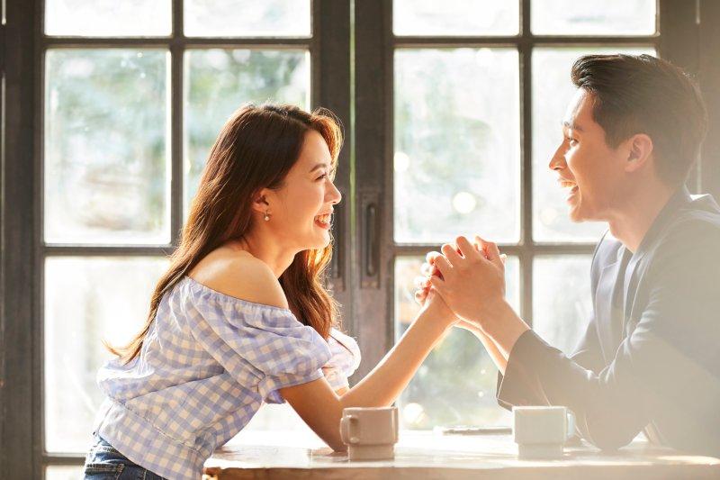 窓辺で手を握り見つめ合うカップル