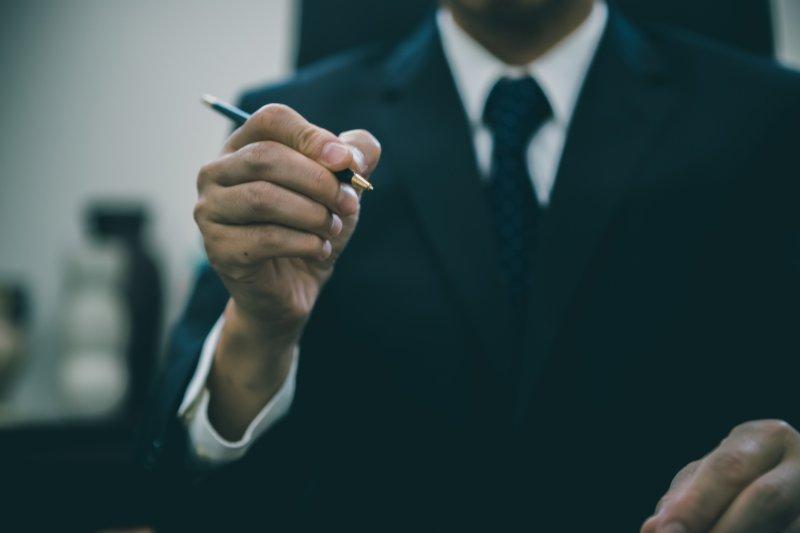 右手にペンを持ったスーツの男性