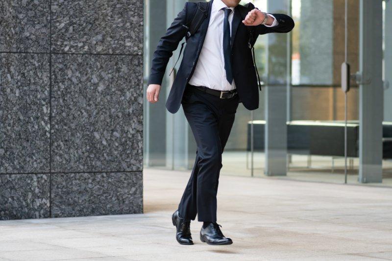 腕時計を見て走り出すビジネスマン