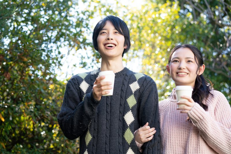 コーヒー片手に腕を組んで歩くカップル