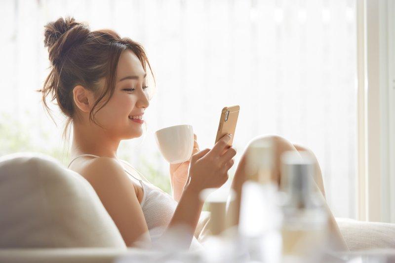 カップで飲み物を飲みながらスマホを見ている女性