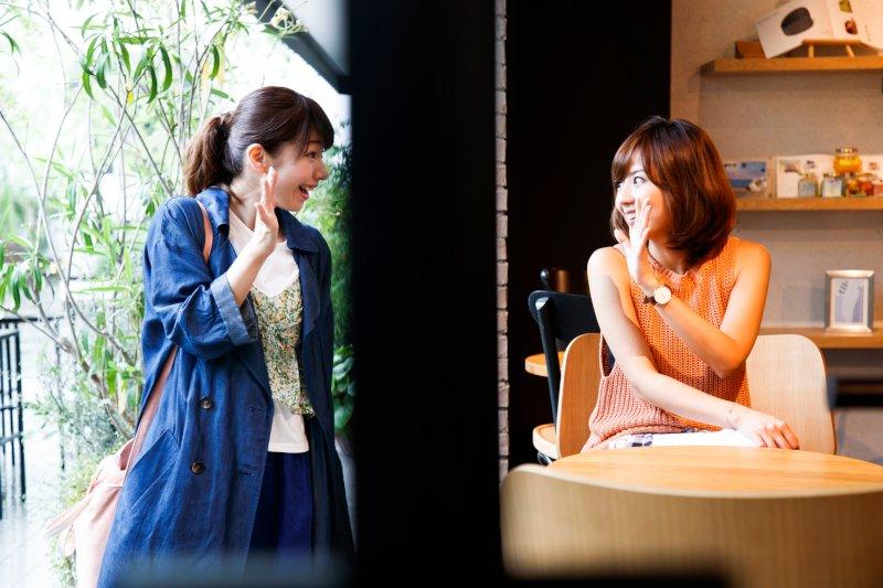 カフェで待ち合わせして手を振り合う2人の女性