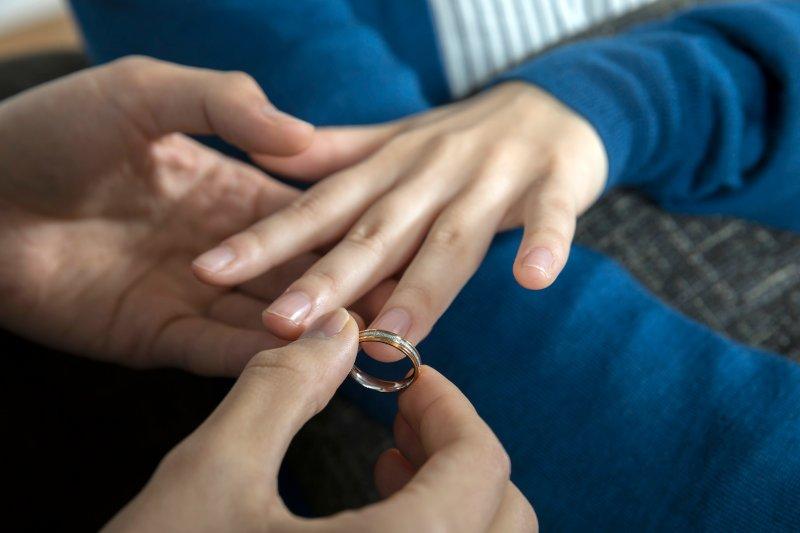 男性が女性の左薬指に指輪をつけようとしている