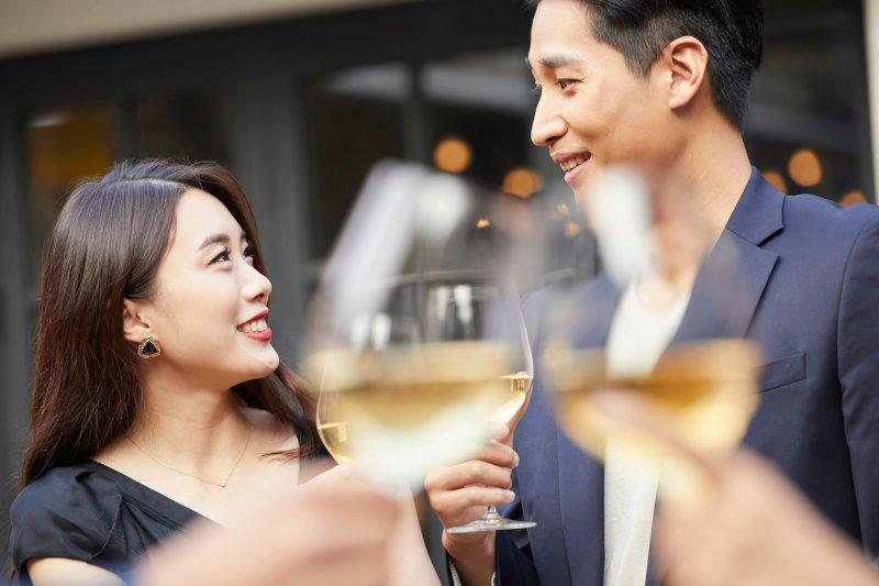 乾杯しているグラスの後ろに写っている男女
