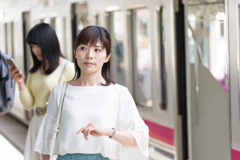 駅で腕時計をつけて時間を気にしている女性