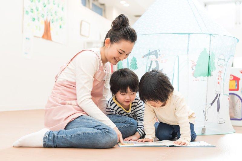 保育士さんが部屋で子供たちと遊んでいる