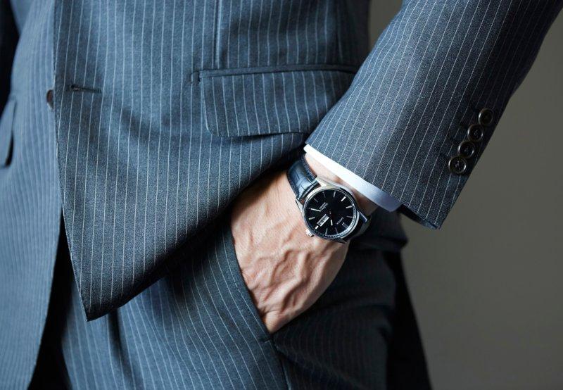 スーツの男性が時計を付けた右手をズボンのポケットに入れている