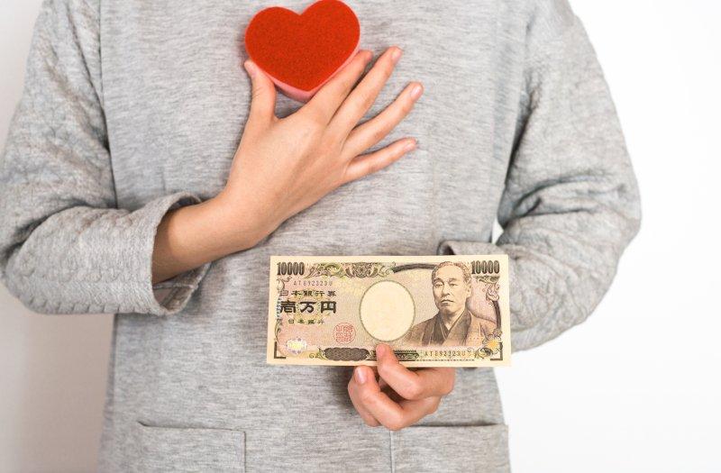 右手にハート左手に1万円札を持っている
