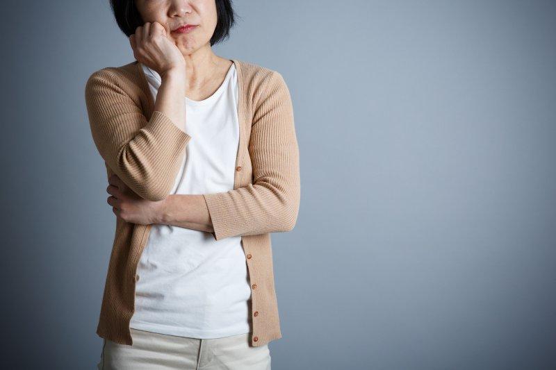 右手で頬杖をして考えている50代女性
