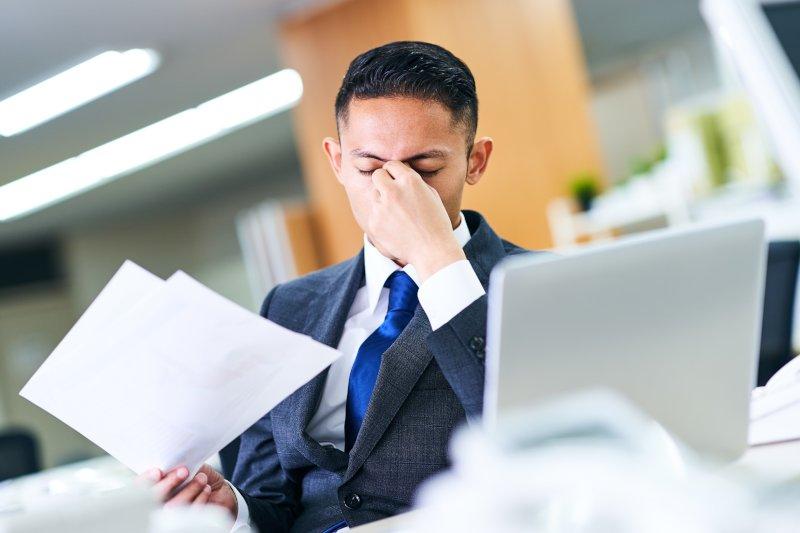 オフィスで働く男性が席に座って疲れている様子