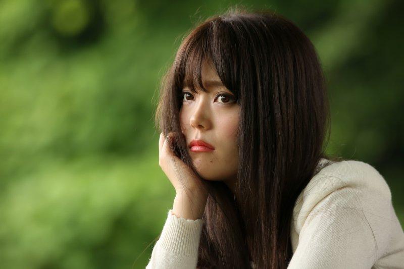 頬杖して悲しそうな表情の女性