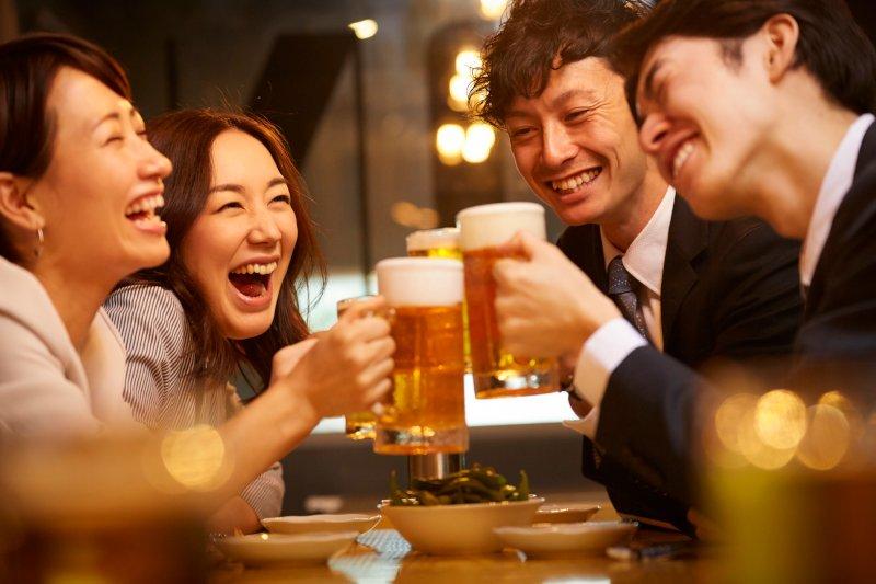 飲み会でビールで乾杯する男女