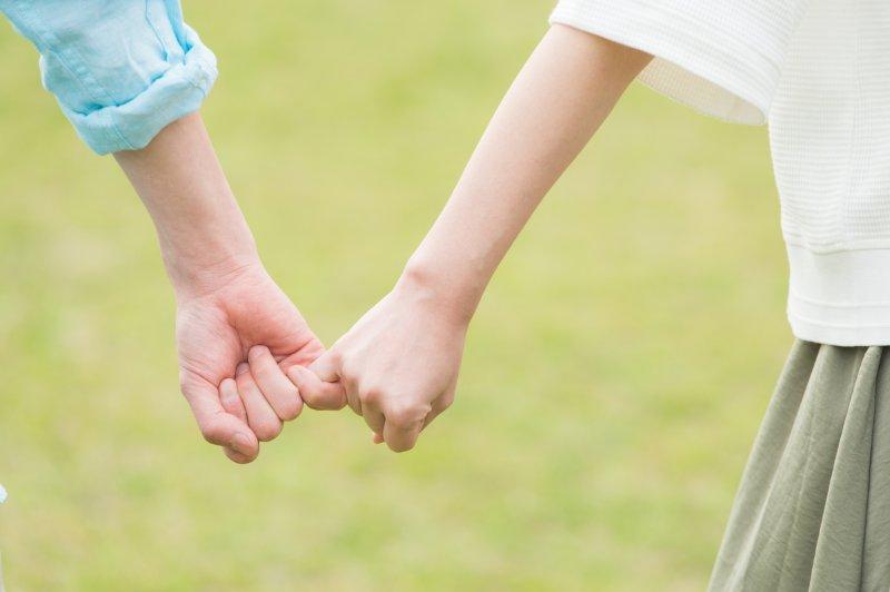 小指を繋いで歩く男女の手元のアップ