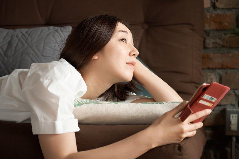 ソファに寝そべりながらスマホを使用する女性