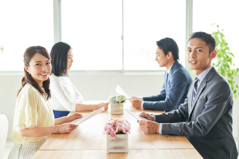 テーブル越しに男女自己紹介している様子