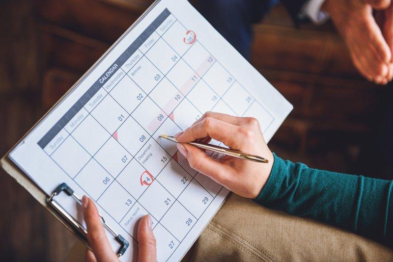 卓上カレンダーに予定を書き込んでいる手元のアップ