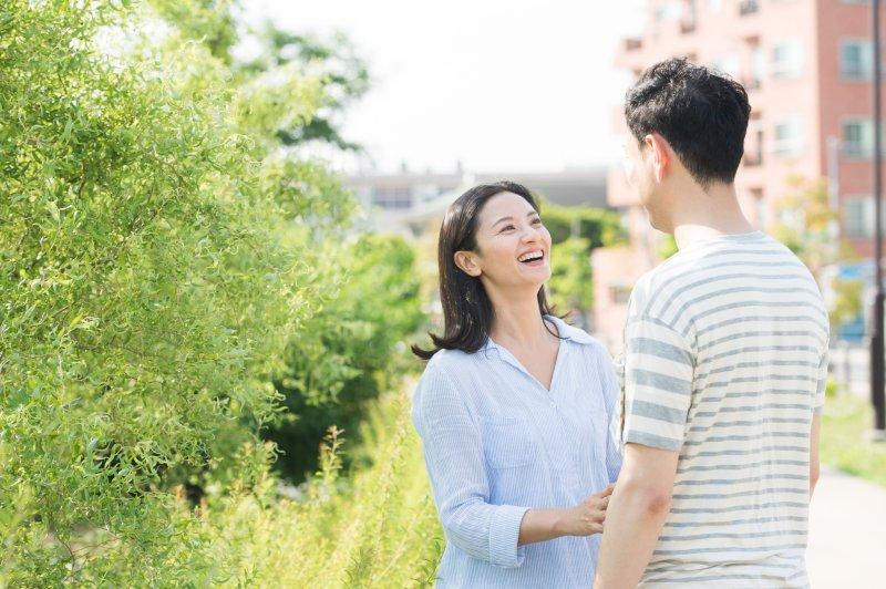 道で向かい合って笑顔で話すカップル