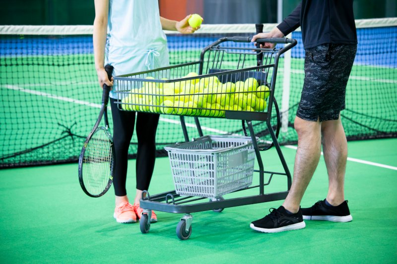 テニスボールが入ったカートの両サイドで会話する男女