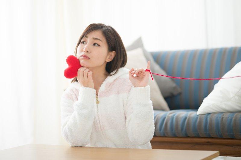 ソファの前に座り右手でハートのオブジェを持ち左の小指に赤い毛糸が繋がっている