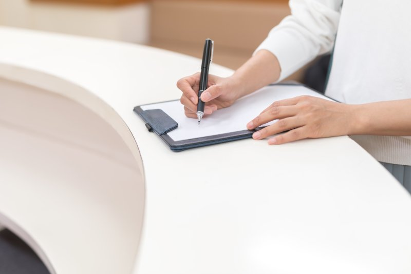 受付で書類を記入する女性の手元のアップ