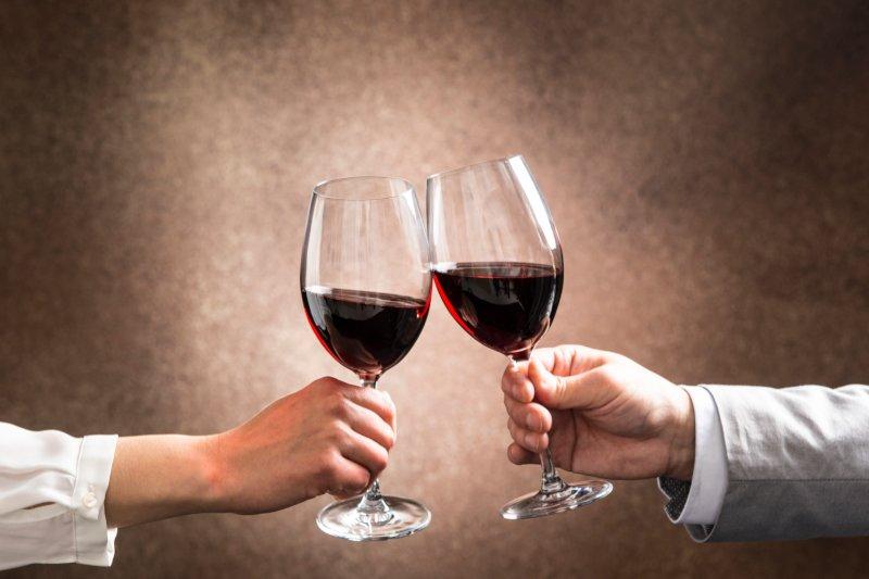 赤ワインで乾杯している男女の手元