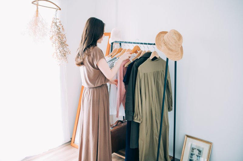 部屋で洋服を選んでいる女性