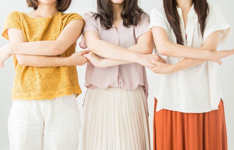 女性3人が腕組をして横に並んでいる